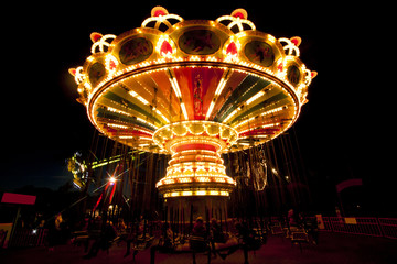 Colorful chain swing carousel in motion at amusement park at night.