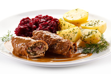 Wrapped pork chops with potatoes and beetroots on white background