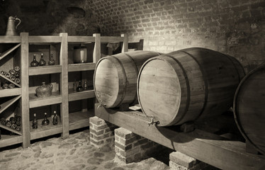 Barrels with a wine in a cellar with a brick wall in background. Black and White Photography. Beautiful vintage.