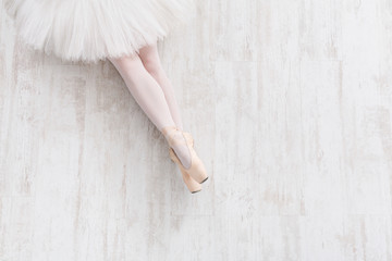 Ballerina in pointe shoes, graceful legs, ballet background