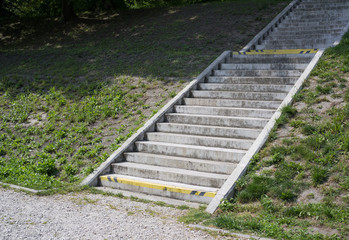 Staircase made of concrete. Green grass is around stairway