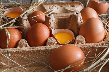 Fresh chicken brown eggs in carton on rustic wood background