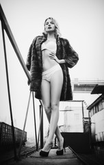 Beautiful sexy young girl in fur coat and underwear stands at railroad station. Full length. Black and white