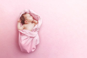 Newborn baby girl sleep on pink blanke