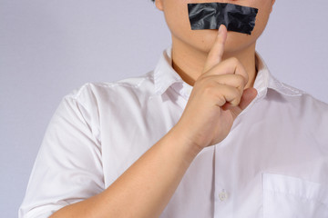 Young Man with black duct tape over his mouth on grey background.