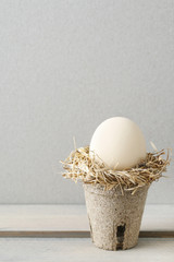 Simple easter decoration with egg and hay wreath.
