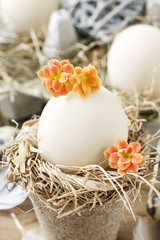 Simple easter decoration with egg, hay wreath and Kalanchoe blossfeldiana flowers.
