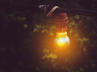 A light bulb on the dark background