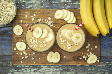 Useful and delicious smoothies. Banana smoothies with oatmeal on a wooden board on a  blue wooden background, top view
