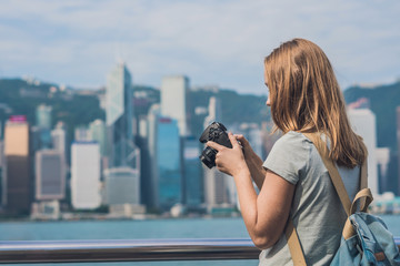Young woman taking photos of victoria harbor in Hong Kong, China