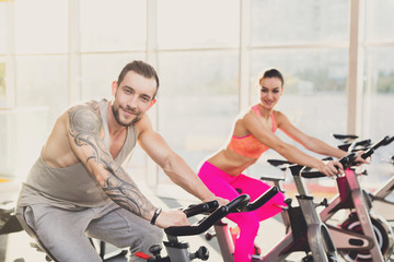 Man and woman, couple in gym on exercise bikes