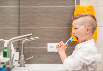 The boy in the bathroom sings with a toothbrush