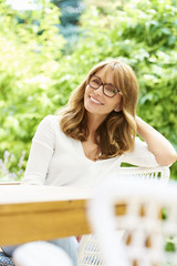 Happy mature woman outdoor portrait. Close-up portrait of an attractive smiling middle aged woman relaxing in the garden at home.