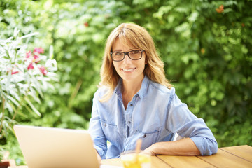 Manage my business from home. Portrait of a beautiful smiling woman using her laptop while sitting at desk outdoor on terrace at home.