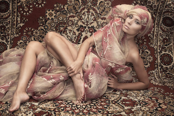 Portrait of a girl model on the background of carpets. Asian culture, east, style, fashion, beauty.