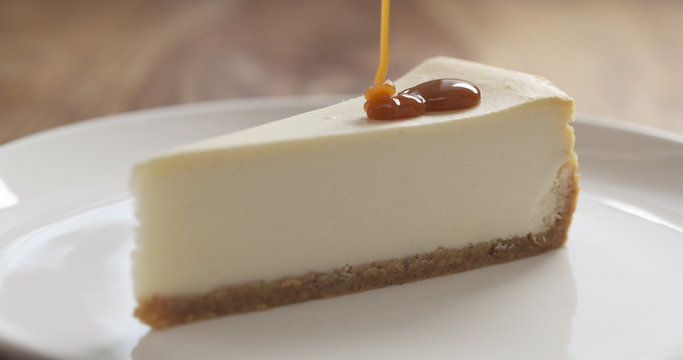 caramel sauce pour on slice of traditional new york cheesecake on white plate on wood table