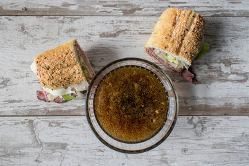 roastbeef sandwich with bowl of beef broth for dipping top view
