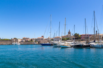 Alghero, Sardinia, Italy. Yachts in the port against the background of medieval fortress walls