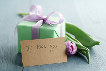 green gift box with purple bow and tulip on blue wood background with i love you greeting card