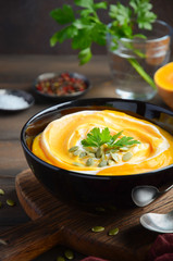 Pumpkin cream soup with cream and pumpkin seeds on wooden background, selective focus