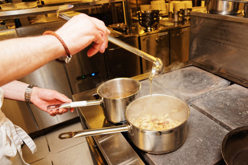 Chef is pouring broth in pot, toned