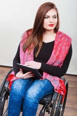 Woman invalid girl on wheelchair using tablet