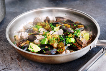 Clams and mussels on hot pan, toned