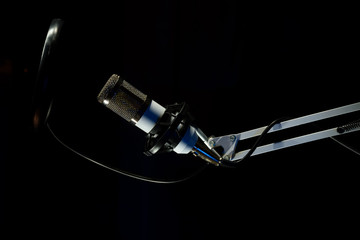 Professional condenser studio microphone on the black background