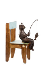 Bronze statuette of a cat sitting on a wooden chair and fishing isolated on a white background
