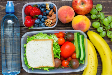 School lunch boxes with sandwich, fresh fruits and vegetables, berries and nuts and bottle of water