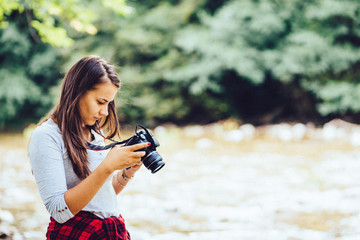 Great looking young girl browsing photos she took with her camera in the forest near the river