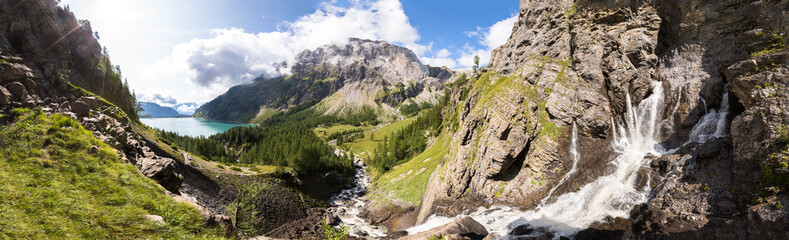 Photo sur Plexiglas Alpes Panorama of torrent stream, lake, green valley in Alps mountains