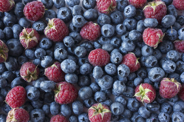 Fresh blueberry and raspberry background. Texture blueberry and raspberry berries close up