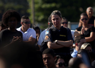 A military policewoman reacts during the funeral of Fabio Cavalcante e Sa, the 100th military police officer who died due to violence this year, in Duque de Caxias, Rio de Janeiro
