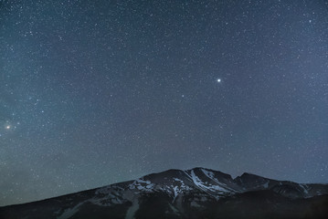 Star filled sky over snowy mountains at night