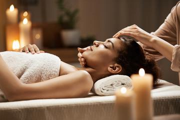 Attractive african girl enjoying face massage in spa salon.