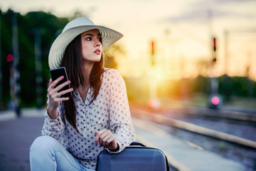 Young woman with baggage on train station using smart phone waiting