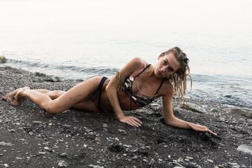 bellissima ragazza giovane bionda ,posa in spiaggia con bikini tipo militare  molto sensuale