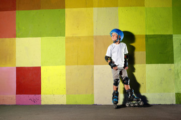 Cute little athletic boy on roller standing against the green yellow graffiti wall