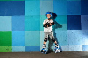 Cute little athletic boy on roller standing against the blue graffiti wall