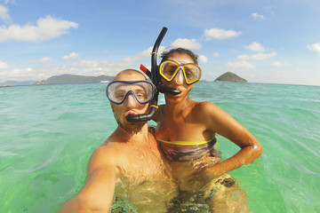 Young Mixed Race Couple Making Selfie Photo Using Waterproof Camera in Clear Ocean after Snorkeling. Phuket, Thailand.