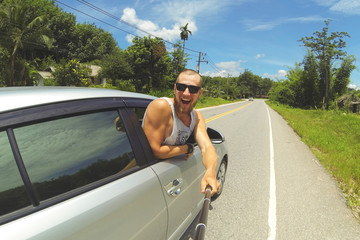 Young Happy Man Taking Selfie Picture with Smartphone on Monopod Stick. Hipster Making Road Trip Photo From Car Window.