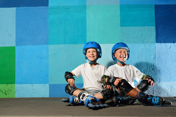 Yong little athletic boys on roller sitting against the blue graffiti wall