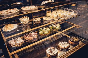 Sweets and cakes in showcase. Italian pastry shop. Cakes with fruits, berries and chokolate