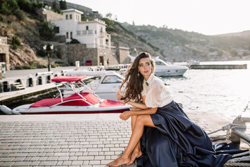 Beautiful girl walking on the pier by the sea near the yacht, boats in the blue long dress