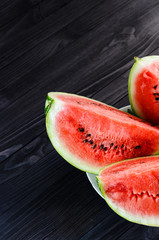 Background of three slices of a cut watermelon in a white plate on a black wooden table top view. Empty space for text