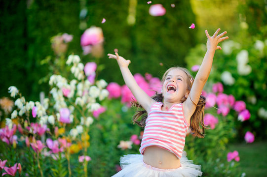 happy little girl ralutsya and jumps on a lawn near flowers, throws petals