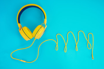 yellow headphones or earphone computer on a blue pastel background