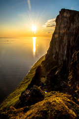 Fjord mountain midnight sun setting over water