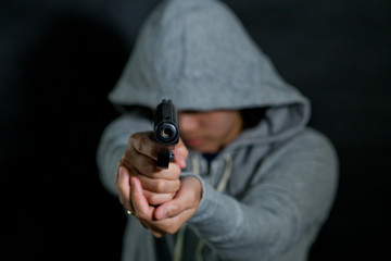 woman pointing  gun  at the target   / selective focus  / killer / safety and criminal concept